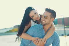 Happy young woman piggyback ride man outdoors in sunset royalty free stock photography