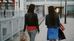 Happy young women friends walking over the bridge with shopping bags, talking discuss, back view, slow mo stedicam shot stock video footage