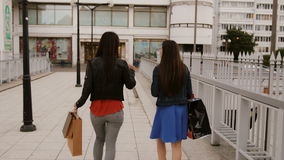 Happy young women friends walking over the bridge with shopping bags, talking discuss, back view, stedicam shot 4K stock footage
