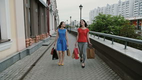 Happy young women friends walking with shopping bags, talking discuss having fun. slow mo stedicam shot stock video