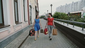 Happy young women friends walking with shopping bags, talking discuss having fun. slow mo stedicam shot stock footage