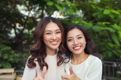 Happy young women friends well-dressed smiling while standing to Stock Photography