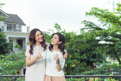 Happy young women friends well-dressed smiling while standing to Royalty Free Stock Photos