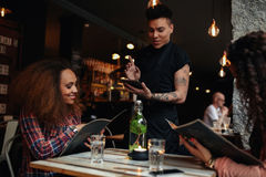 Happy young women giving order to the waiter. Happy young people sitting in restaurant reading menu card and giving orders to the male waiter, while waiter Stock Photos