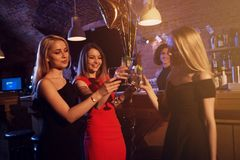 Happy young women with glasses of wine and cocktails enjoying a night out in stylish bar.  Royalty Free Stock Photography