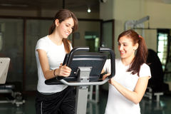 Happy young women in the gym biking Royalty Free Stock Photo