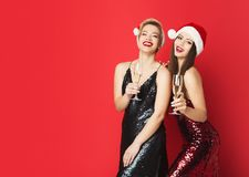 Happy girl friends having New Year party in trendy outfits. Happy young women having New Year party, drinking champagne over red background, copy space Royalty Free Stock Image
