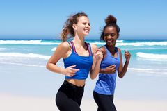 Happy young women jogging on the beach Royalty Free Stock Photos