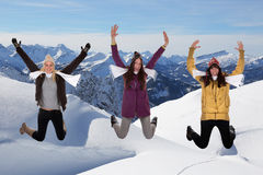 Happy young women jumping in winter in the mountains Stock Photos