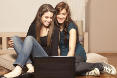 Happy young women with laptop on the floor Royalty Free Stock Image