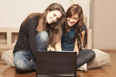 Happy young women with laptop on the floor Royalty Free Stock Photo
