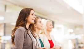 Happy young women in mall or business center. Sale, consumerism and people concept - happy young women in mall or business center Royalty Free Stock Image