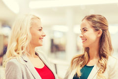 Happy young women in mall or business center. Sale, consumerism and people concept - happy young women in mall or business center Stock Photography