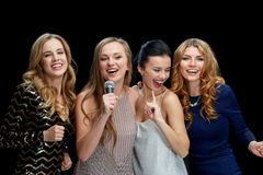 Happy young women with microphone singing karaoke Stock Photo