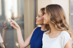 Happy young women pointing finger to shop window Royalty Free Stock Images