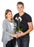 Anniversary gift. Happy young women receiving a white orchid from his boyfriend on anniversary day Royalty Free Stock Images