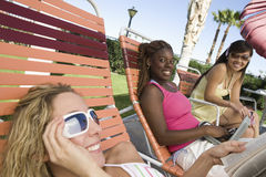 Happy Young Women Relaxing On Deck Chair Royalty Free Stock Photos