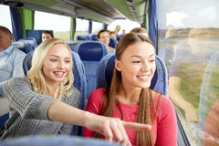 Happy young women riding in travel bus. Transport, tourism, friendship, road trip and people concept - young women or teenage friends riding in travel bus Royalty Free Stock Photography