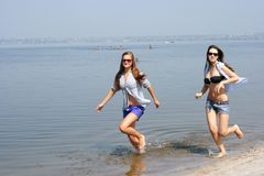 Happy young women running across the beach Royalty Free Stock Photos