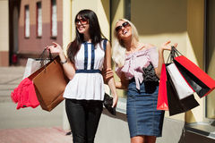 Happy young fashion women with shopping bags walking on city street Royalty Free Stock Image
