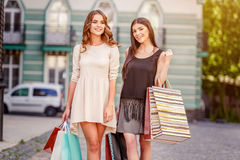 Happy young women with shopping bags. Happy young caucasian women with shopping bags outdoor Royalty Free Stock Images