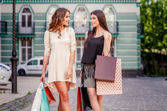 Happy young women with shopping bags. Happy young caucasian women with shopping bags outdoor Royalty Free Stock Photos
