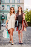 Happy young women with shopping bags. Happy young caucasian women with shopping bags outdoor Royalty Free Stock Image