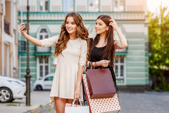 Happy young women with shopping bags. Happy young caucasian women with shopping bags outdoor Stock Images