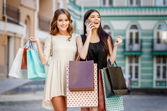 Happy young women with shopping bags Royalty Free Stock Images