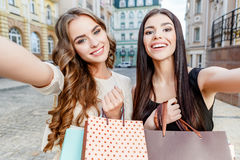 Happy young women with shopping bags Stock Photos