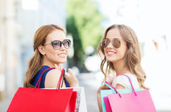 Happy young women with shopping bags in city Royalty Free Stock Images