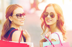 Happy young women with shopping bags in city Royalty Free Stock Image