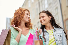 Happy young women with shopping bags in city Royalty Free Stock Photo
