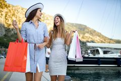 Happy young women with shopping bags enjoying in shopping. Consumerism, shopping, lifestyle concept. Happy women with shopping bags enjoying in shopping stock images