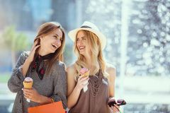 Happy young women with shopping bags and ice cream having fun. On city street Stock Photo