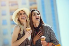 Happy young women with shopping bags and ice cream having fun. On city street Stock Photos
