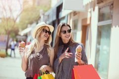 Happy young women with shopping bags and ice cream having fun. On city street Royalty Free Stock Photography