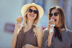 Happy young women with shopping bags and ice cream having fun. On city street Royalty Free Stock Photo