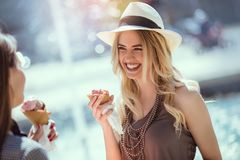 Happy young women with shopping bags and ice cream having fun. On city street Royalty Free Stock Images