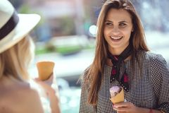 Happy young women with shopping bags and ice cream having fun. On city street Stock Photography