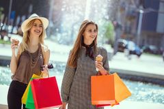 Happy young women with shopping bags and ice cream having fun. On city street Stock Image