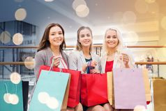 Happy young women with shopping bags in mall. Sale, consumerism and people concept - happy young women with shopping bags in mall Stock Photo