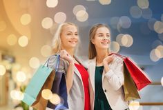 Happy young women with shopping bags in mall. Sale, consumerism and people concept - happy young women with shopping bags in mall Royalty Free Stock Photos