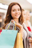 Happy young women with shopping bags in mall Stock Photo