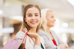 Happy young women with shopping bags in mall Royalty Free Stock Photos