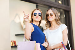 Happy young women with shopping bags in mall Royalty Free Stock Image