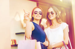 Happy young women with shopping bags in mall. Sale, consumerism and people concept - happy young women with shopping bags pointing finger at shop window in city Royalty Free Stock Image