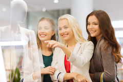 Happy young women with shopping bags in mall. Sale, consumerism and people concept - happy young women with shopping bags pointing finger to shop window in mall Royalty Free Stock Image