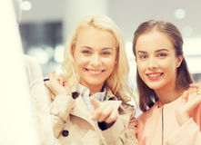Happy young women with shopping bags in mall. Sale, consumerism and people concept - happy young women with shopping bags pointing finger to shop window in mall Stock Photos