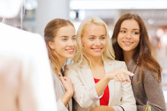 Happy young women with shopping bags in mall. Sale, consumerism and people concept - happy young women with shopping bags pointing finger to window in mall Stock Photo